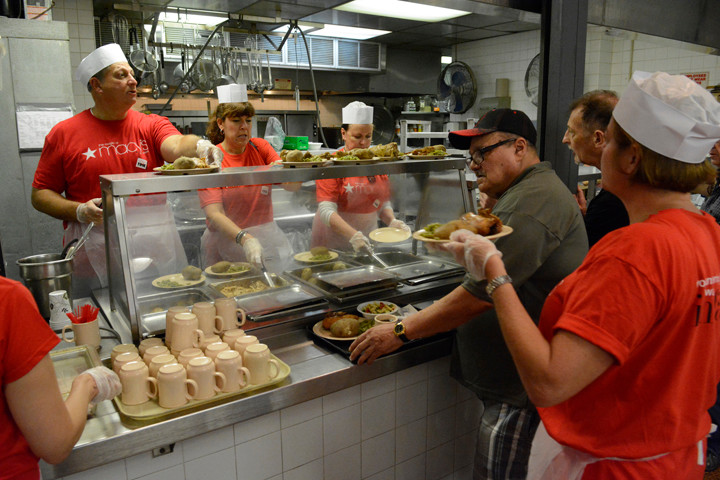 Jeff Kantor, Macy's chief merchandising officer, back left, along with members of Macy's leadership team, prepare and serve lunch to senior citizens July 26 at the Encore Senior Center at St. Malachy's parish in Manhattan.