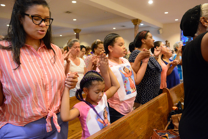 Congregants joins hands for the Lord's Prayer.