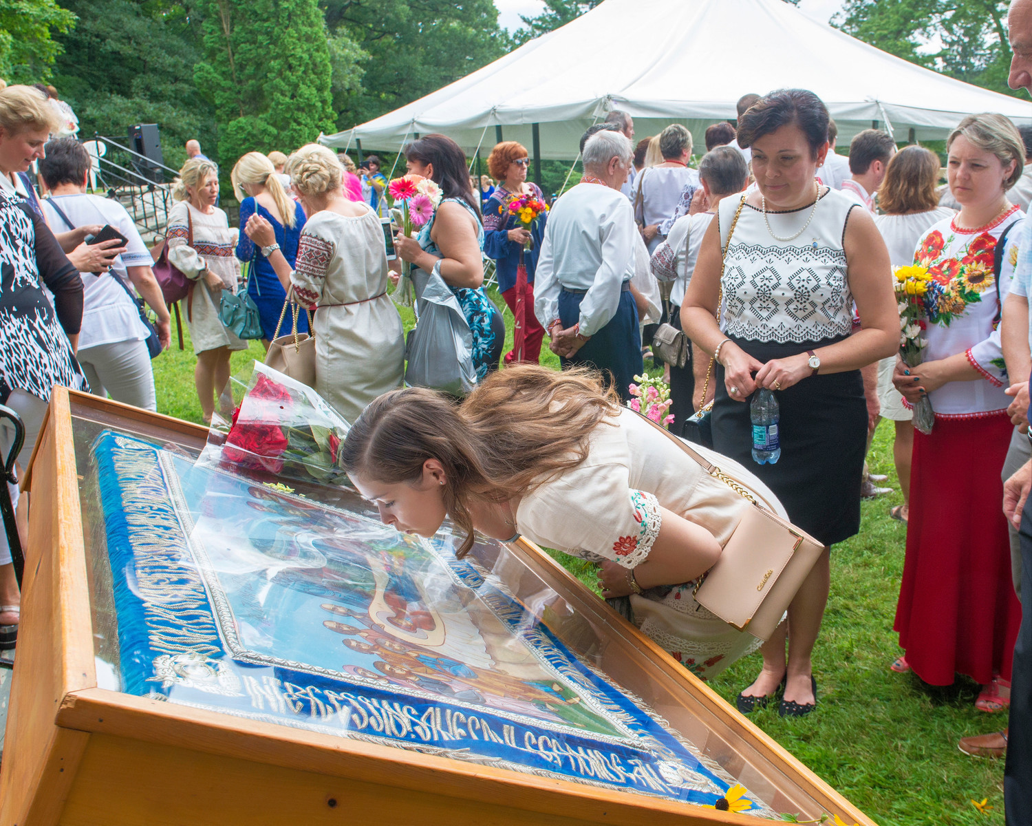 "A young woman kisses the tapestry of ""The Falling Asleep of the Mother of God"" at the pilgrimage."
