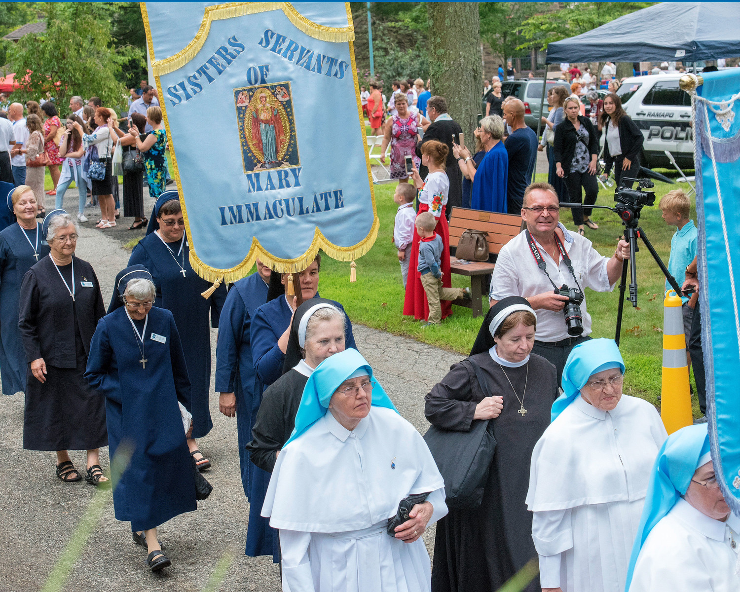 The Sisters Servants of Mary Immaculate, who hosted the event, carry their banner in the procession.