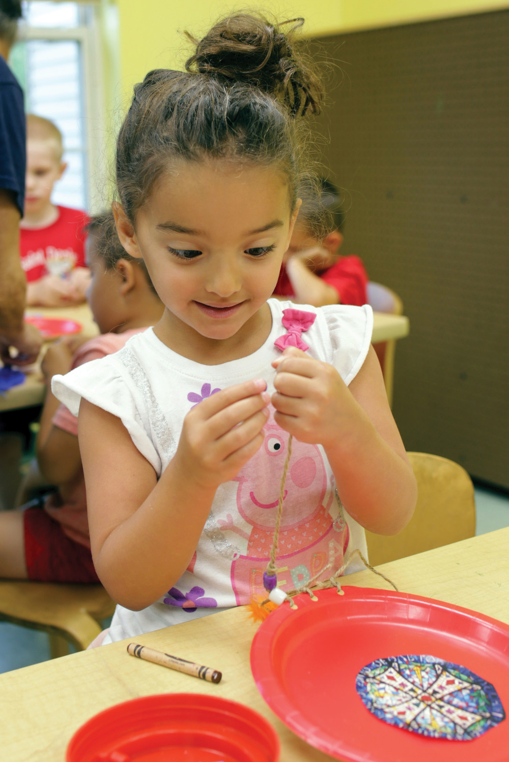 Chloe Colucci, who is entering kindergarten, takes part in a craft activity.