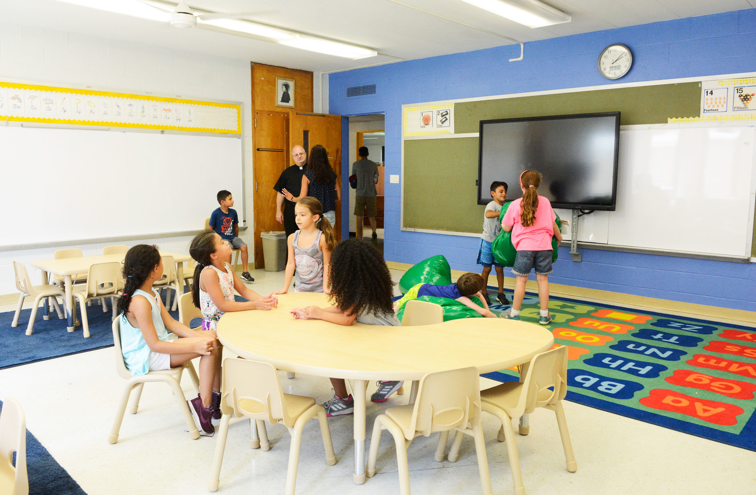 Students visit one of the remodeled classrooms in St. Elizabeth Ann Seton School during an open house Aug. 8, as Father Robert Quarato, pastor of the parish, looks on.