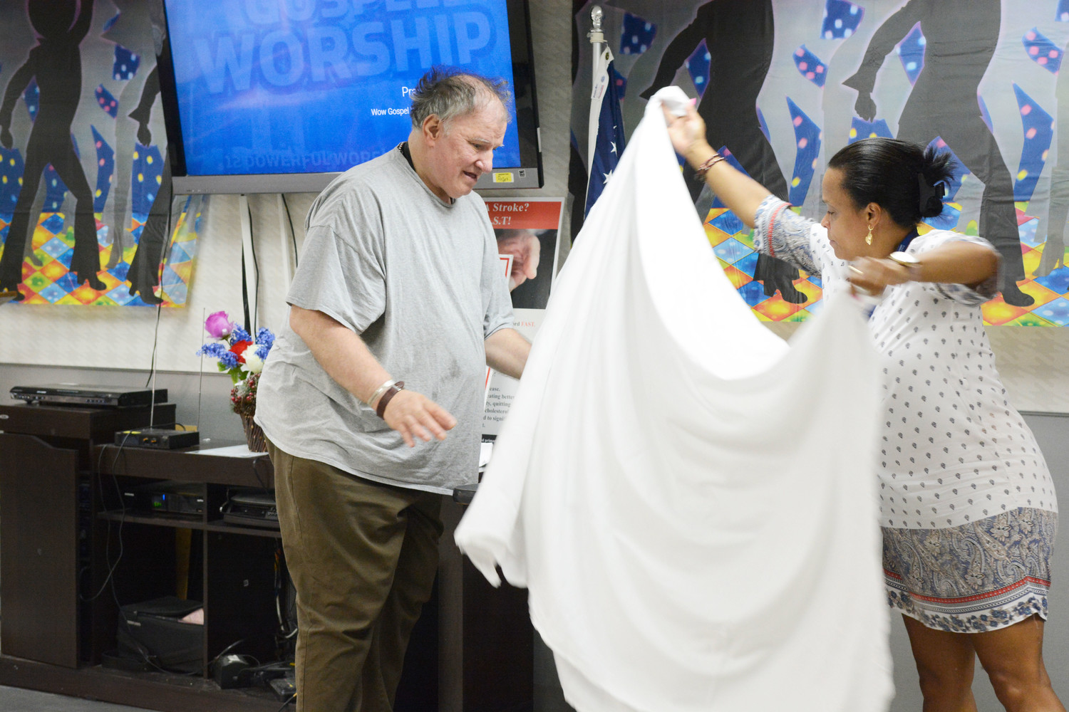 Donald Baumgaertner, a resident of East Haven Nursing and Rehabilitation Center, the Bronx, assists Bernadette Dubois, recreation leader at East Haven, with an altar cloth in preparing the center for Mass Aug. 24.