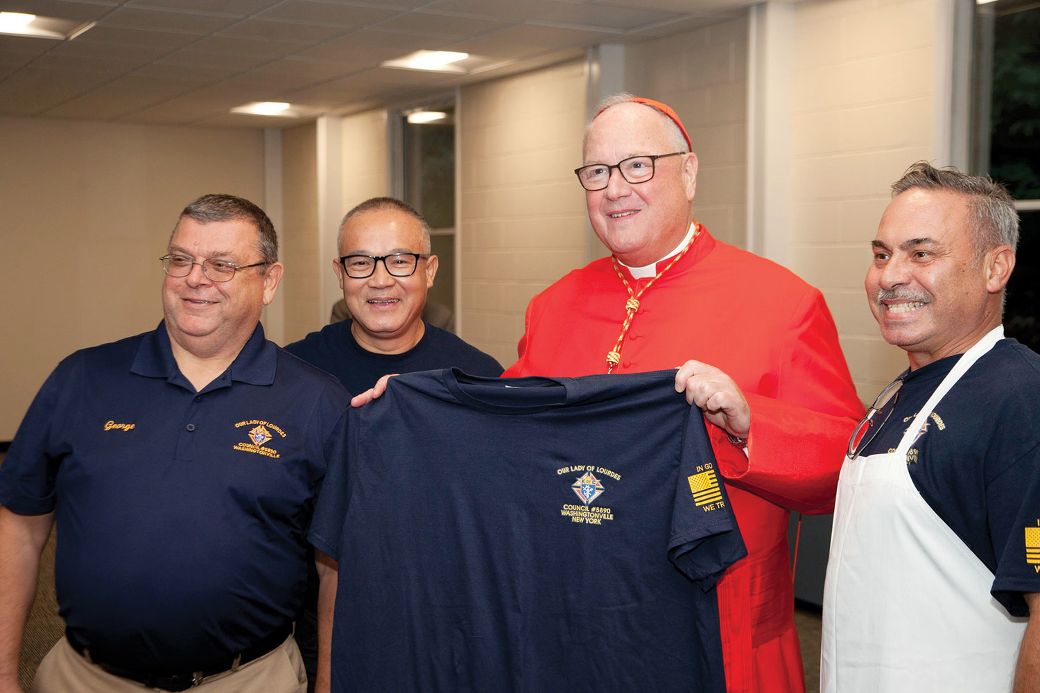 George Eismount, Lu Pham and Viz Cordero, left to right, make Cardinal Dolan an honorary member of the Our Lady of Lourdes Knights of Columbus Council 5890 at St. Mary's in Washingtonville Sept. 7. Cardinal Dolan visited the parish for vespers and to bless the new parish center.