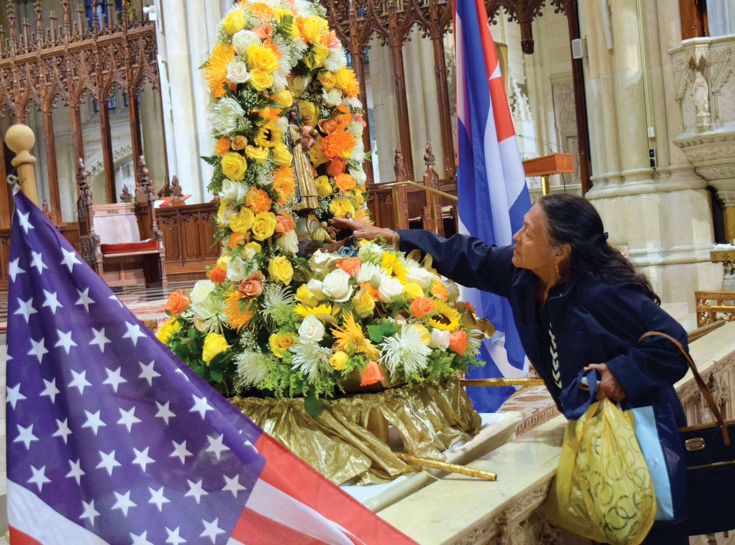 A woman reaches out to the image of Our Lady of Caridad del Cobre.