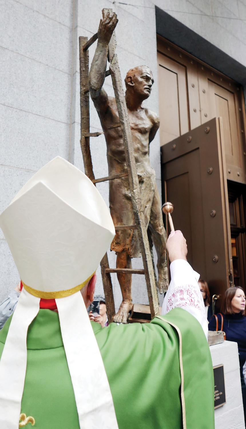 The cardinal blesses a sculpture of St. Florian, patron saint of firefighters and EMS workers. It is one of four bronze statues that grace the top of the steps outside the church and part of a 9/11 Catholic Memorial there.