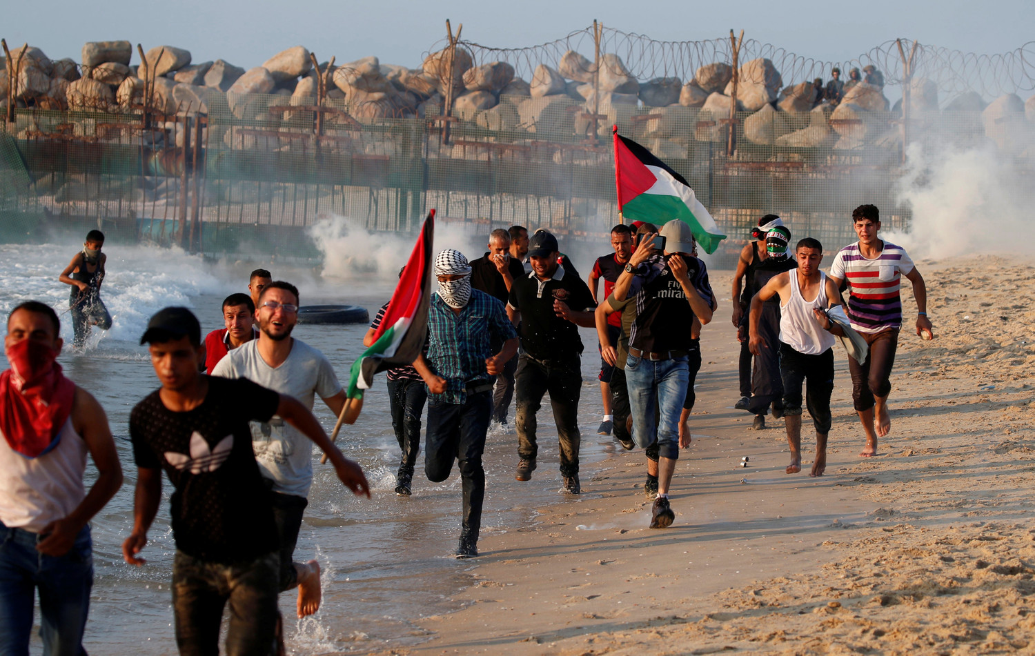 Palestinians run for cover from tear gas fired by Israeli troops during a Sept. 10 protest along a beach in the Gaza Strip. The U.S. budgetary cuts to humanitarian aid institutions providing assistance to Palestinians in Gaza and the West Bank could lead to long-term disastrous consequences, said aid workers in the region.