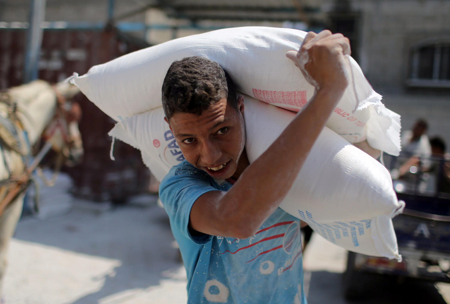 A Palestinian youth carries bags of flour Sept. 3 at an aid distribution center in Khan Younis, Gaza Strip. The U.S. budgetary cuts to humanitarian aid institutions providing assistance to Palestinians in Gaza and the West Bank could lead to long-term disastrous consequences, said aid workers in the region.