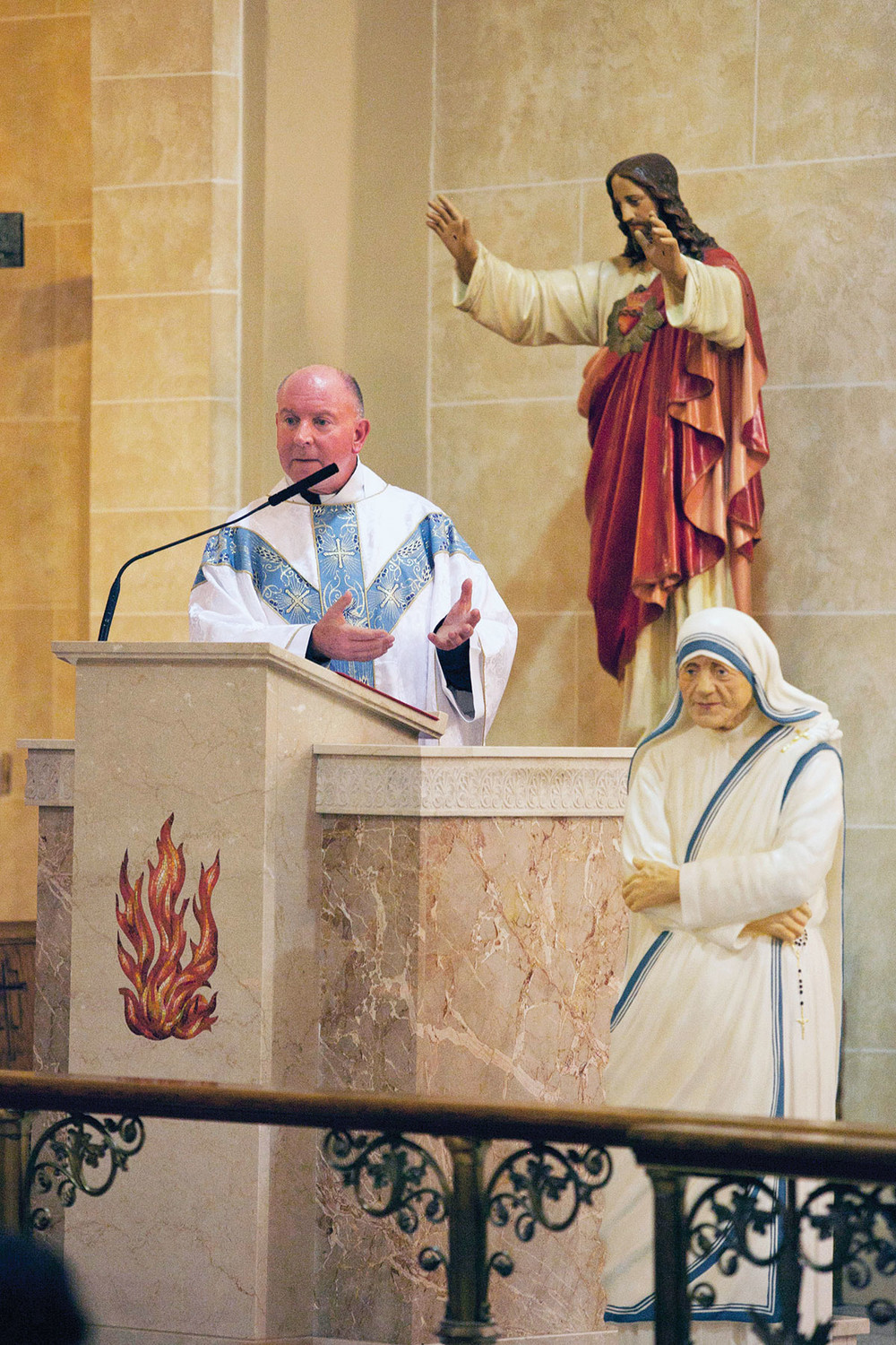 Father Damroth, pastor of St. Francis of Assisi and Sacred Heart churches, announces the name of the new merged parish in Newburgh as the Parish of St. Mother Teresa of Calcutta, the first parish in the archdiocese named after St. Mother Teresa. A statue of St. Mother Teresa was unveiled as the parish's new name was announced.