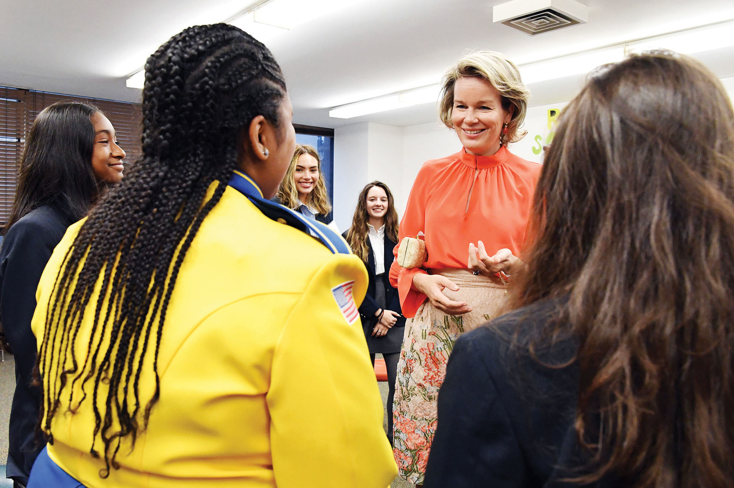 Queen Mathilde talks with the students, who were selected to meet with her in a classroom.