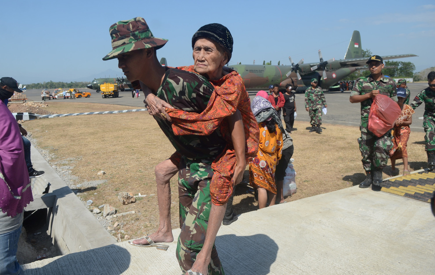 An Indonesian soldier carries an elderly woman during an evacuation Oct. 1 after an earthquake and tsunami on Sulawesi Island.