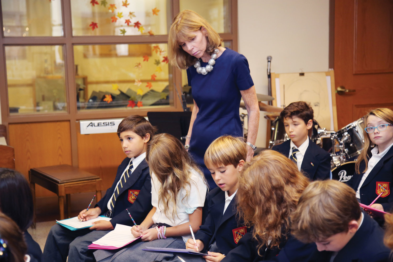 Principal Mary Larkin observes third-graders as they learn how to compose music.