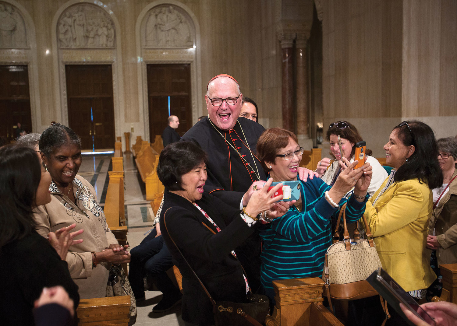 Many pilgrims sought to include the cardinal in a group photo at the shrine.