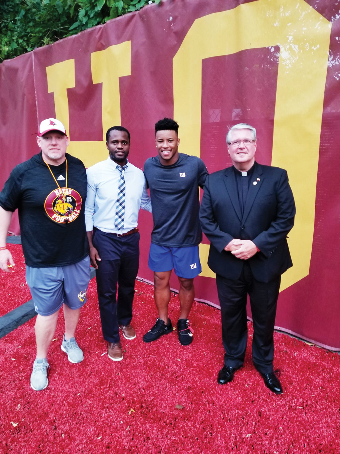 Barkley, second from right, joins CJ O'Neil, Cardinal Hayes varsity football coach; Craig Joseph, assistant principal in charge of enrollment and sports management; and Father Joseph Tierney, school president.