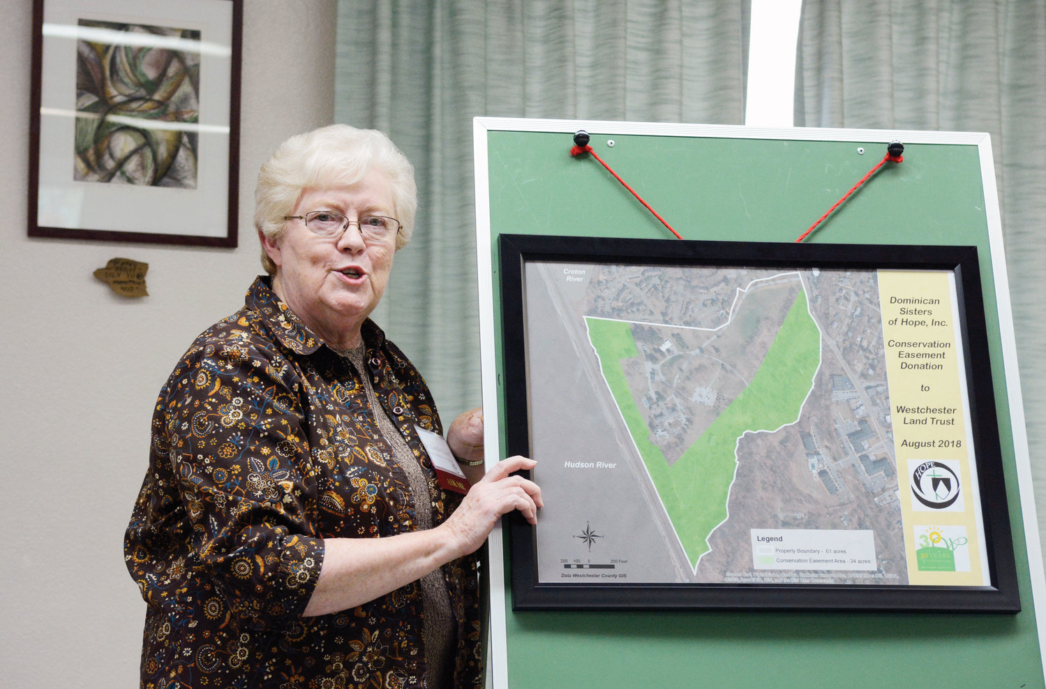 Sister Lorelle Elcock, O.P., prioress of the Dominican Sisters of Hope, discusses the conservation easement, using a map of the property, at the press conference.
