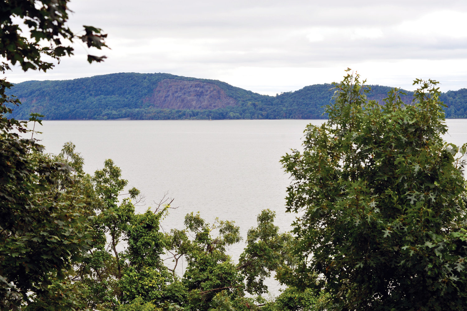 A view beyond the trees at Mariandale shows the Hudson River and the landscape of Rockland County.