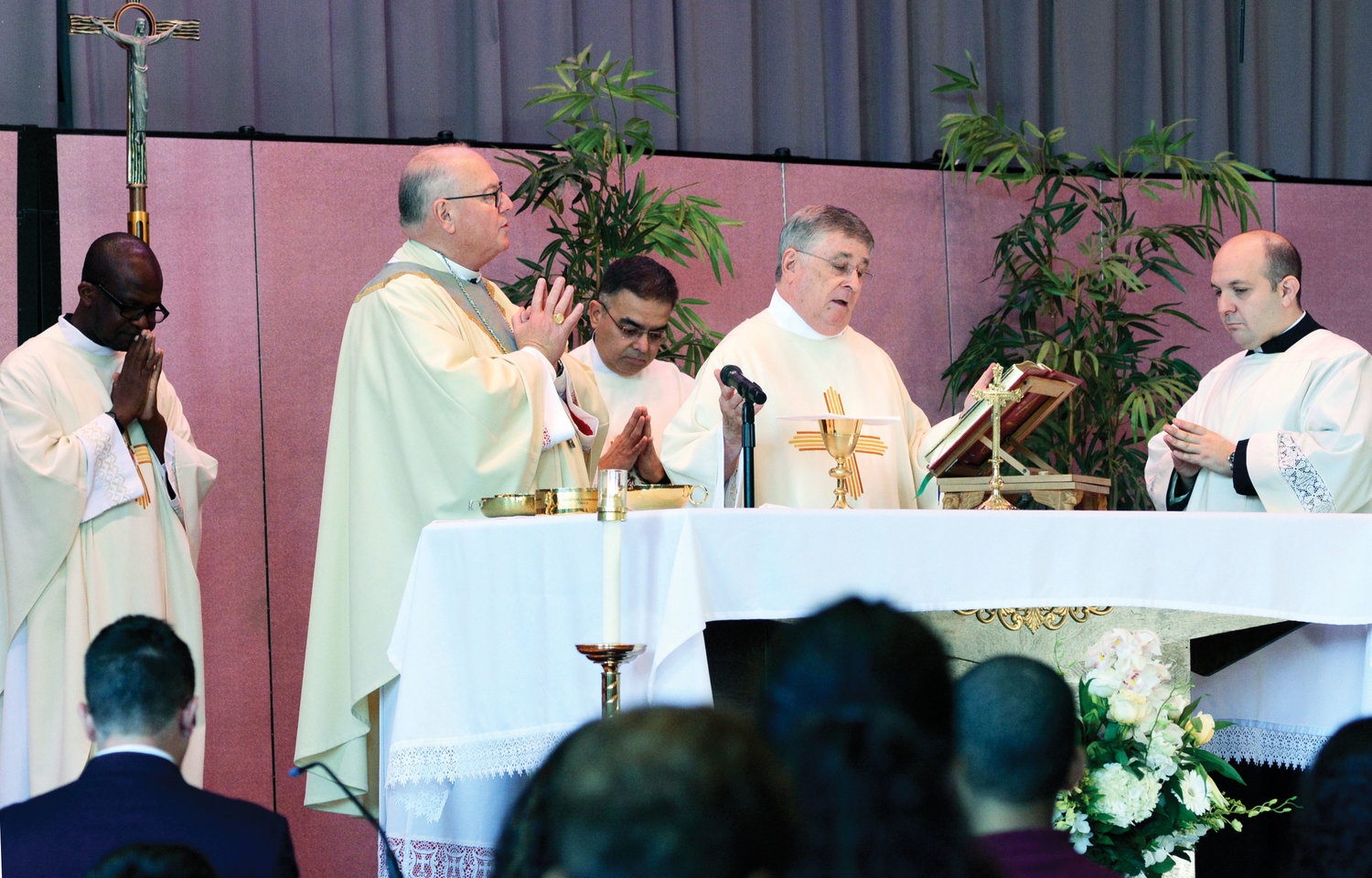 Msgr. John Graham, former pastor of St. Raymond and now pastor of St. Frances de Chantal in the Bronx and dean of the East Bronx, prays during the morning liturgy. Father James Cruz, pastor of St. Raymond, stands between the cardinal and Msgr. Graham.