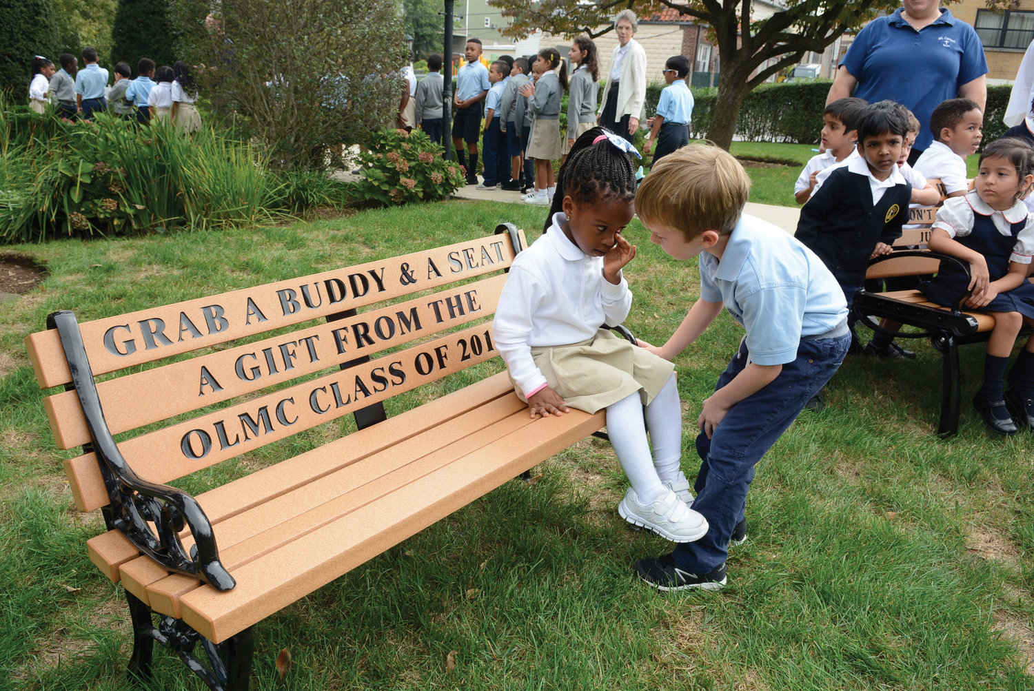 Countess Mmuo and Jackson Masella, first-graders at Our Lady of Mount Carmel School in Elmsford, top, demonstrate the concept behind a buddy bench installed on their school playground.