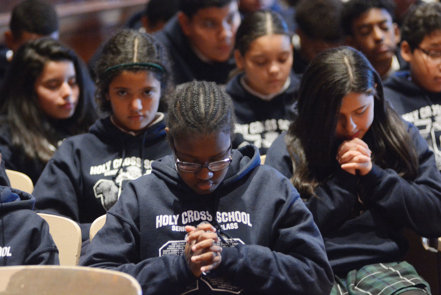 Students from Holy Cross School pray.