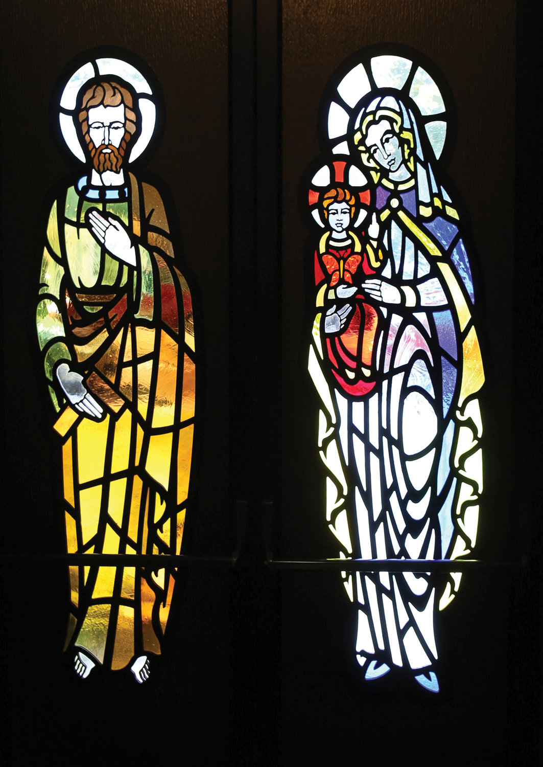 Stained-glass windows are embedded into the main doors exiting Holy Name of Mary.