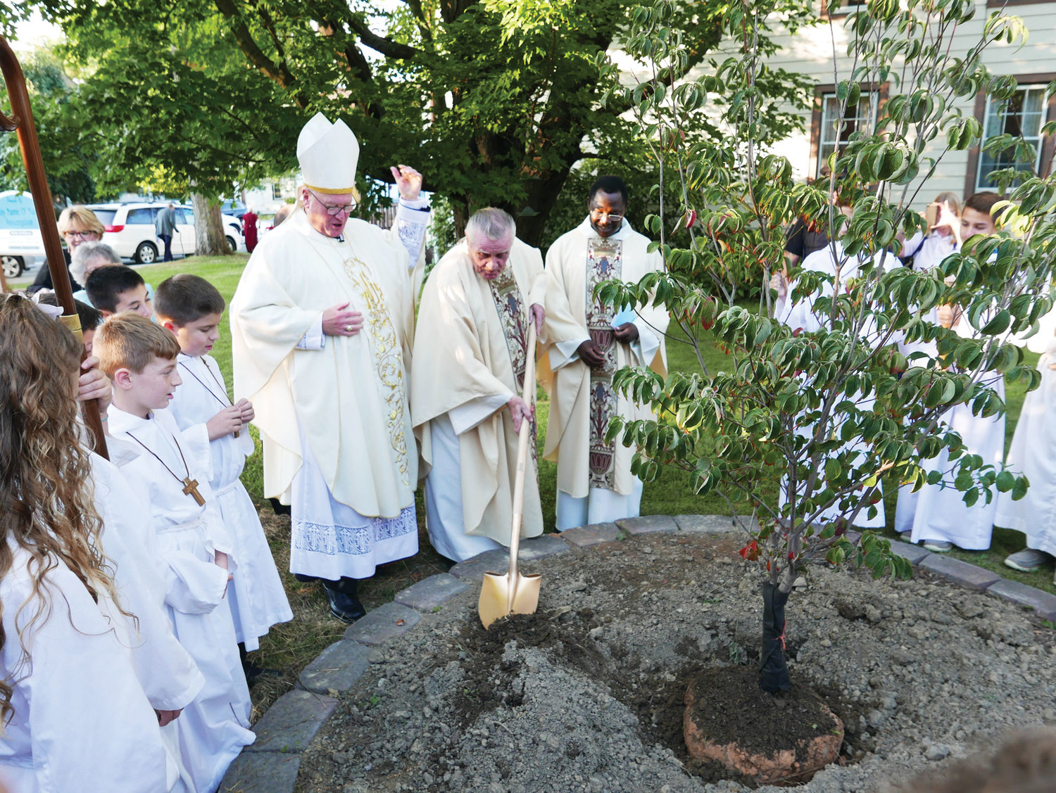 Father Daniel O'Hare, parish administrator of Holy Name of Mary-Assumption, plants a tree following Mass.