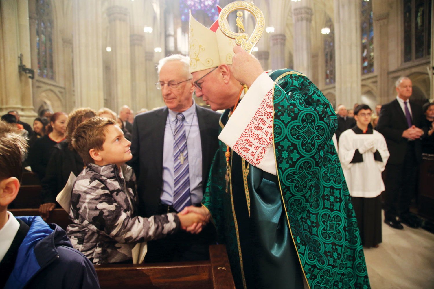 Cardinal Dolan shakes the hand of Maddox Elbert, grandson of Tom Scheuring, center, at Mass at St. Patrick's Cathedral on World Mission Sunday, Oct. 21. Tom Scheuring and his late wife, Lyn, founded LAMP Ministries (Lay Apostolic Ministries with the Poor) 37 years ago to serve the poor through Catholic evangelization.