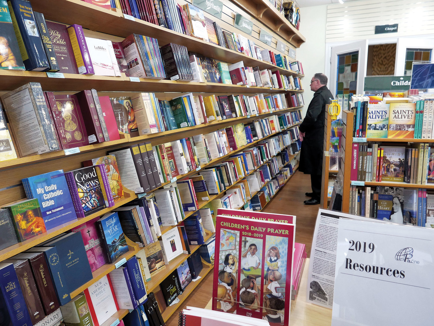 A patron browses selections stacked on neatly lined shelves. The center, operated by the Daughters of St. Paul, moved to its new location at 115 E. 29th St., between Park and Lexington avenues, in April 2017. The sisters invite visitors to attend speaker events and workshops, and to pray in the Eucharistic Chapel.