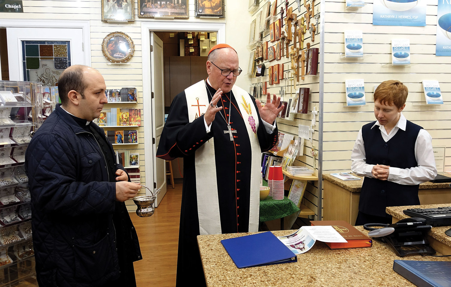 Cardinal Dolan blesses the new Pauline Book & Media Center in Manhattan Oct. 22, as Sister Amanda Detry, F.S.P., a novice with the Daughters of St. Paul, looks on. Assisting the cardinal at left is his priest secretary, Father James Ferreira.