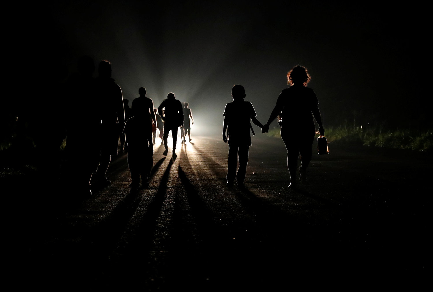 DARK OF NIGHT—A migrant woman, part of a caravan traveling to the United States, holds a child's hand as they walk along a road in the dark Nov. 2 in Huixtla, Mexico. The U.N. children's agency estimates that 2,300 children were traveling in the caravan.