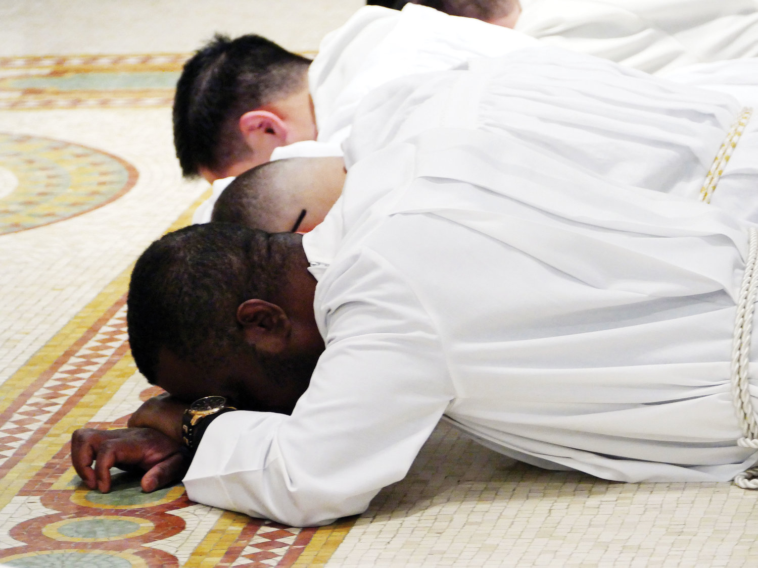 Three men lie prostrate in the sanctuary of the seminary chapel during the Rite of Ordination.