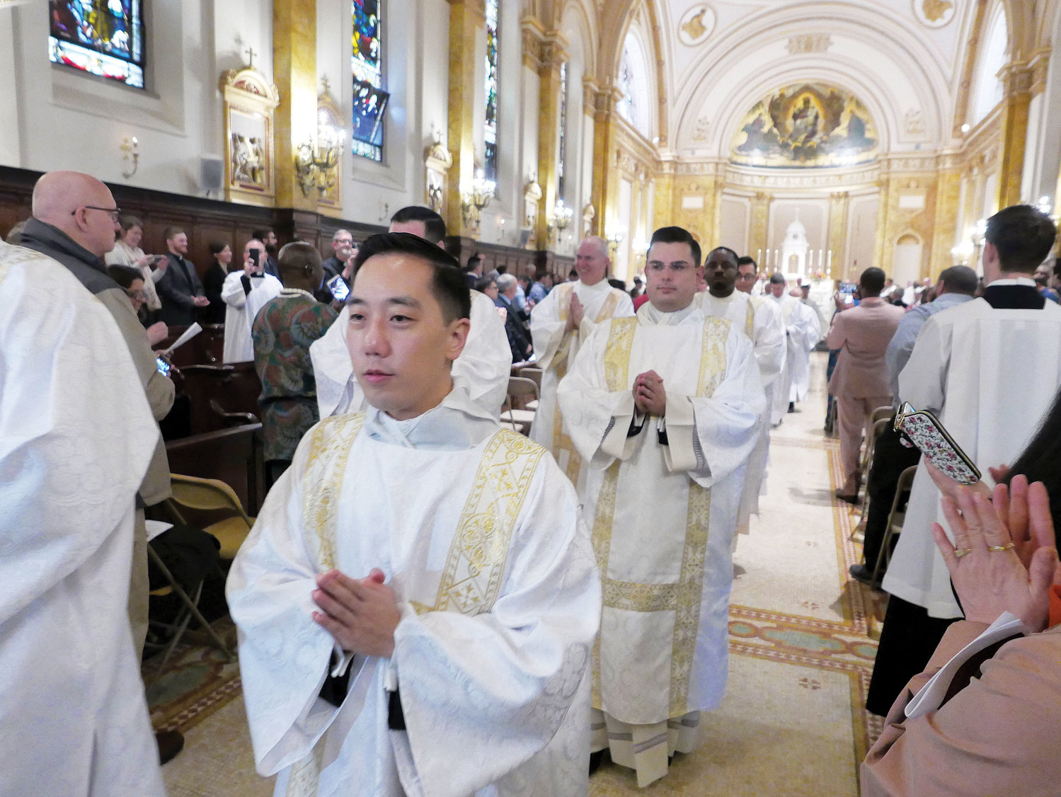Deacon Roger Kwan leads the newly ordained deacons in the recessional.