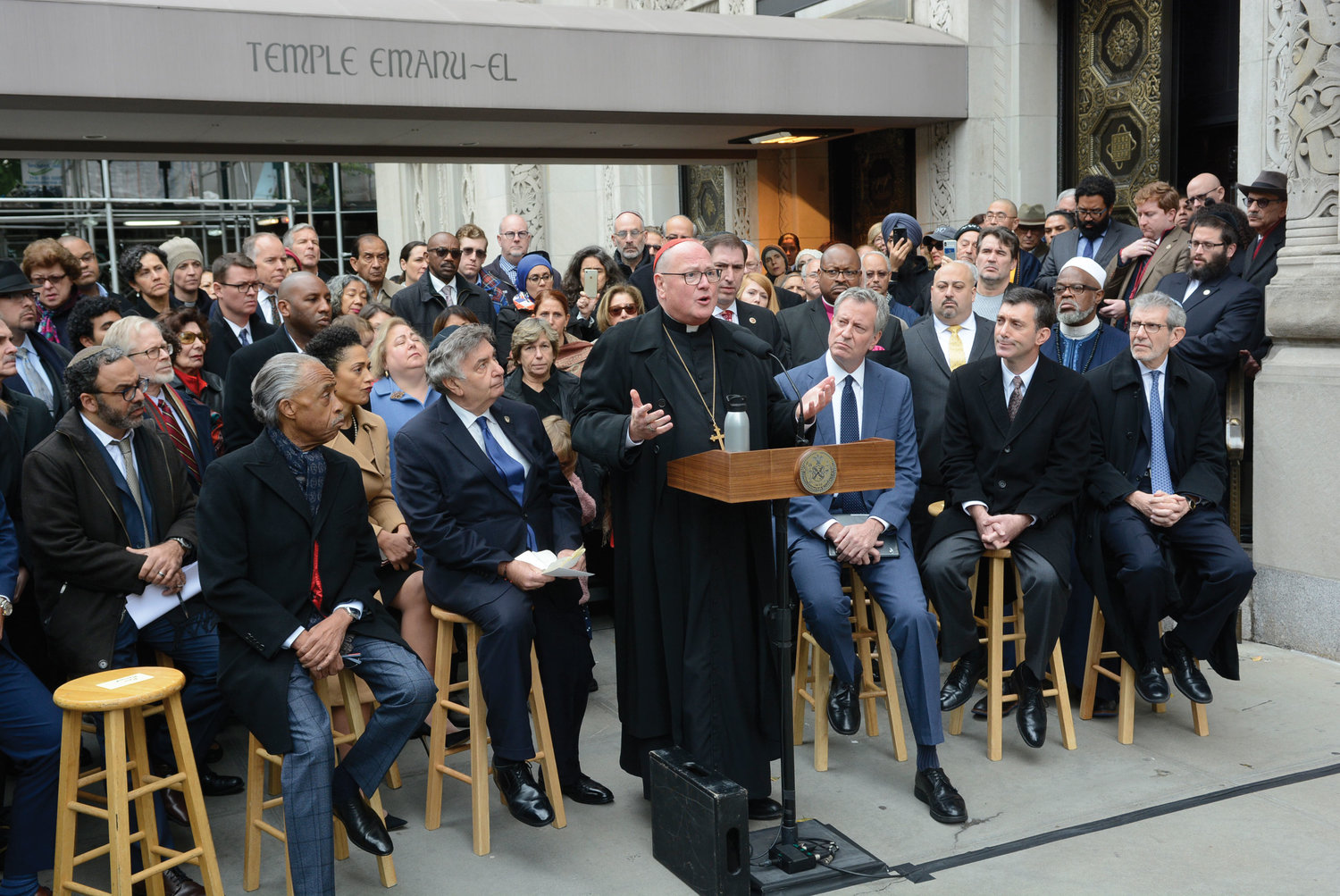 Cardinal Dolan delivers remarks at a press conference outside Temple Emanu-El on Manhattan's Upper East Side on Oct. 28. To the cardinal's immediate left are Rev. Al Sharpton and Rabbi Joseph Potasnik. At his immediate right are Mayor Bill de Blasio and Rabbi Joshua Davidson. Seated at far right is Rabbi Michael Miller, executive vice-president and CEO of the Jewish Community Relations Council of New York.