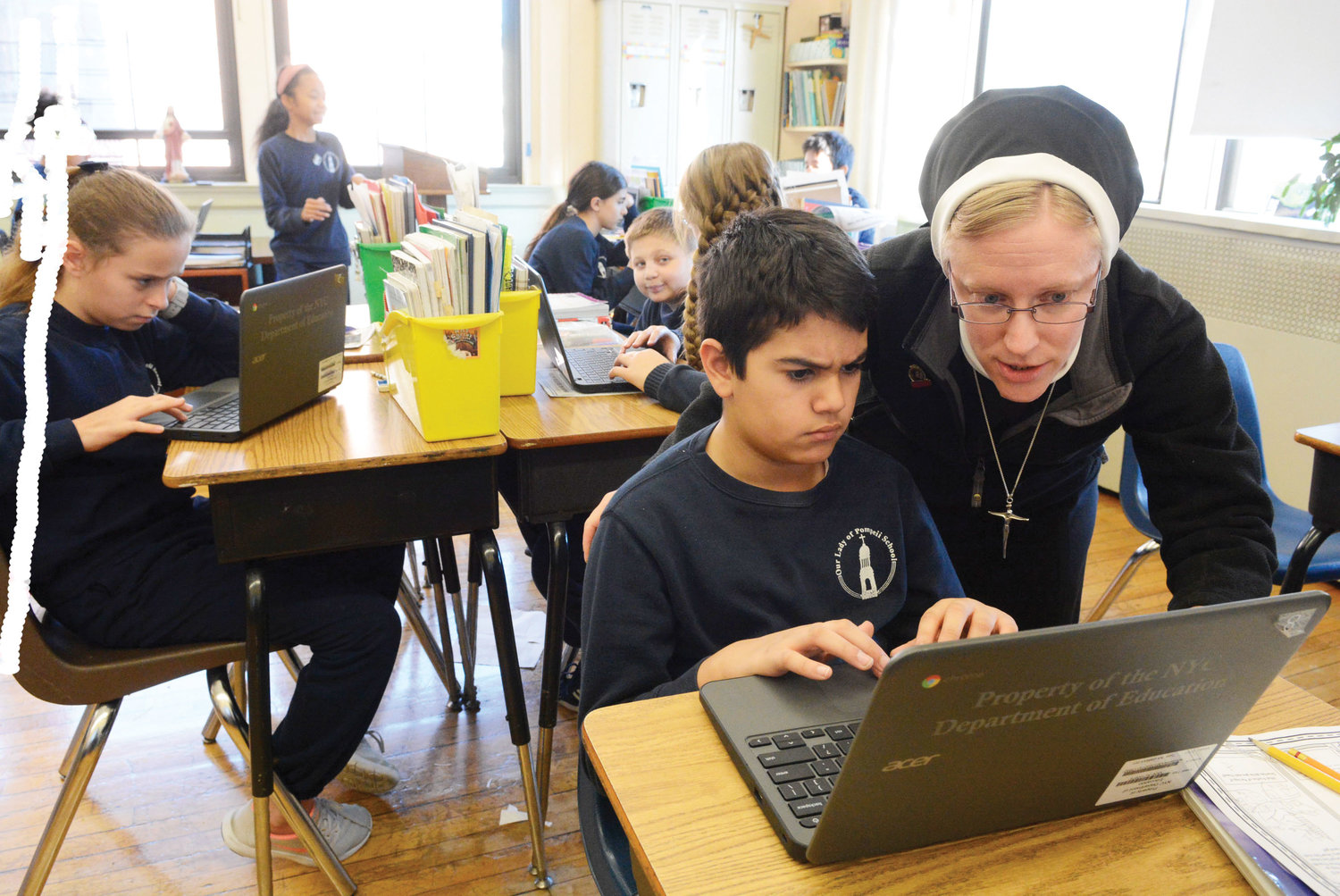 Sister Kathryn assisted a student during fifth grade math class at Our Lady of Pompeii School.