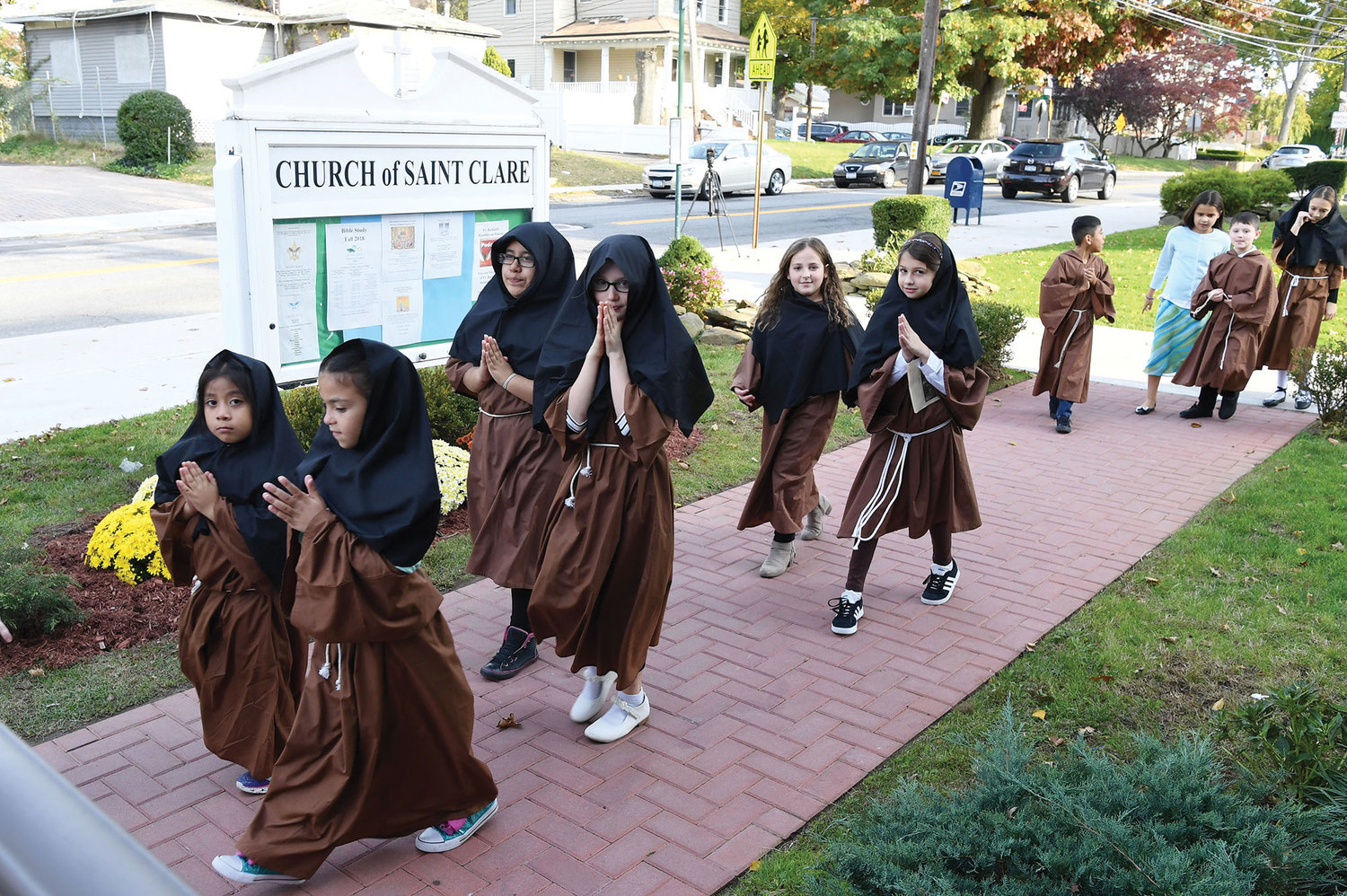 Religious education students, dressed as saints, process to church before the Mass.
