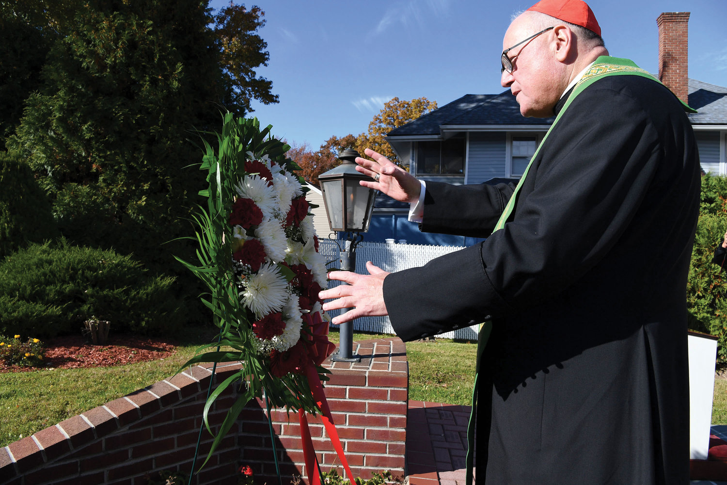 Cardinal Dolan pauses at the wreath next to St. Clare's 9/11 memorial dedicated to the 29 parishioners who died at the World Trade Center on Sept. 11, 2001, during his visit to the Staten Island parish where he led a prayer service for St. Clare School students and celebrated Mass on the eve of All Saints Day with religious education students.