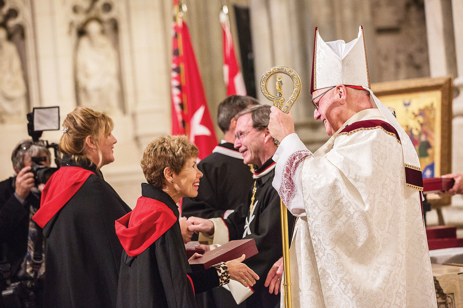 Cardinal Dolan, above right, who served as principal celebrant and homilist, congratulates a new dame after she received her encased Cross of the Order.