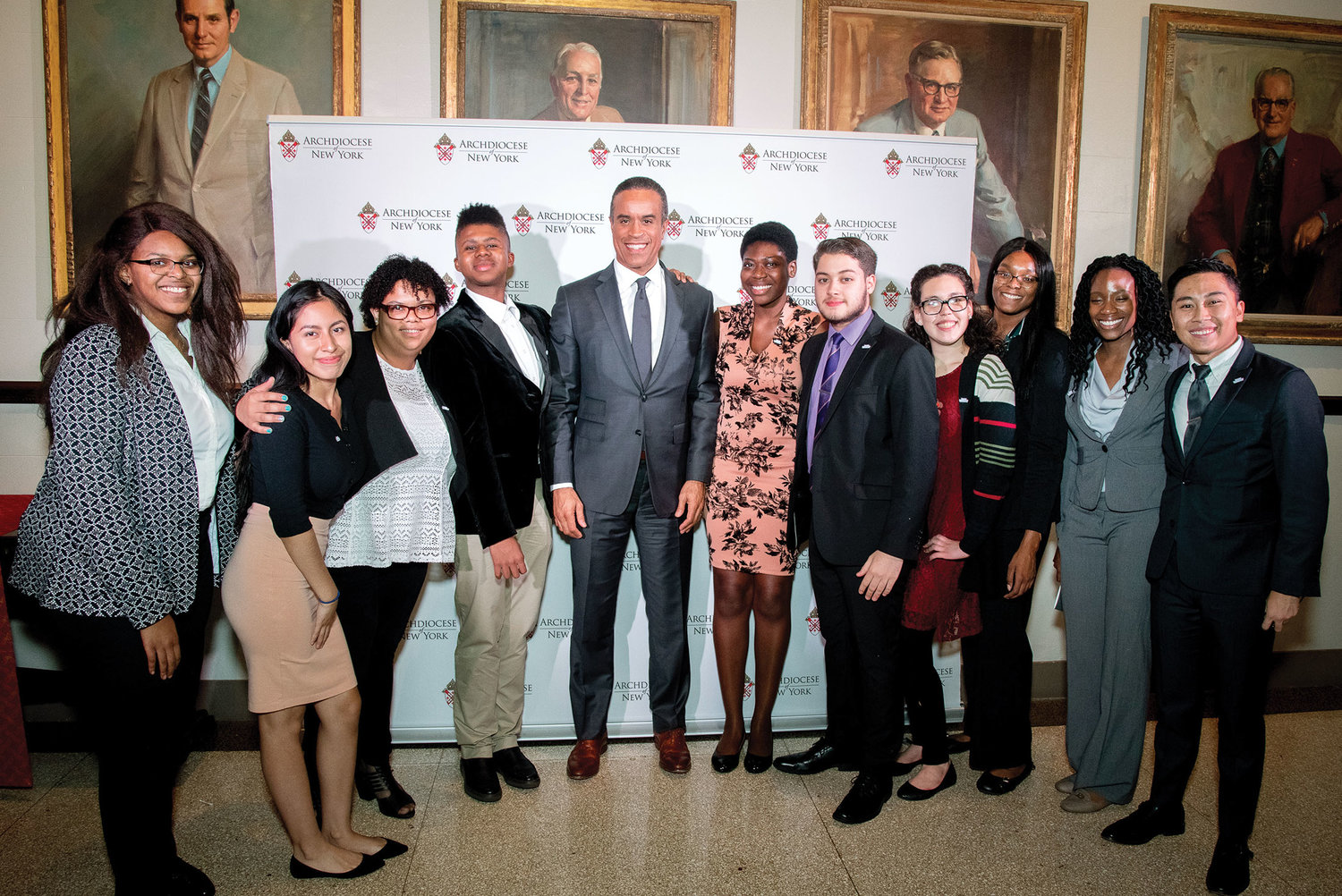 Maurice DuBois, an anchor with WCBS-TV, served as master of ceremonies; he is joined by current recipients of the college scholarship award.