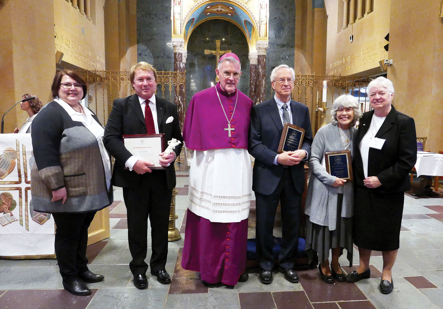 Holding a miniature statue, is Robert Fitkin, who received the Good Shepherd Award. Recipients of the Terence Cardinal Cooke Award included Tom Scheuring and, to his right, Janis Batewell. At far right is Sister Joan Curtin, C.N.D., director of the Catechetical Office and, at far left, Ela Milewska, executive director of the Office of Youth Faith Fcatechists conferred the Catechetical Medal of Honor for 25 years or more of service.ormation.