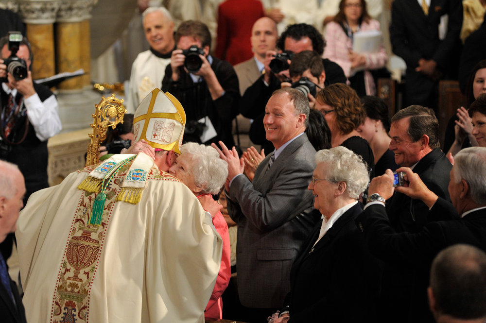 FAMILY moment—Then-Archbishop Dolan receives a congratulatory hug from his mother, Shirley Dolan, at his Mass of Installation as Archbishop of New York in April 2009. Looking on with a smile is his brother, Bob Dolan.