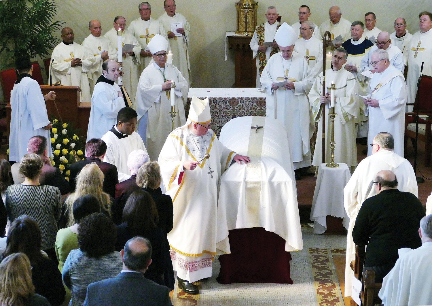 Cardinal Dolan blesses the casket of Retired Auxiliary Bishop Robert A. Brucato, who served as vicar general, chancellor and a pastor of the archdiocese, as well as a military chaplain. The cardinal celebrated the Funeral Mass on Veterans Day, Nov. 12, at the John Cardinal O'Connor Pavilion Chapel in the Riverdale section of the Bronx. Holding the cardinal's staff, is a nephew of Bishop Brucato, Deacon Anthony Bellitto Jr. of the Archdiocese of Philadelphia, who served as Deacon of the Eucharist and Deacon of the Word. Behind the cardinal, to his immediate left and right, are Retired Auxiliary Bishops Dominick Lagonegro and Gerald Walsh, who were principal concelebrants.