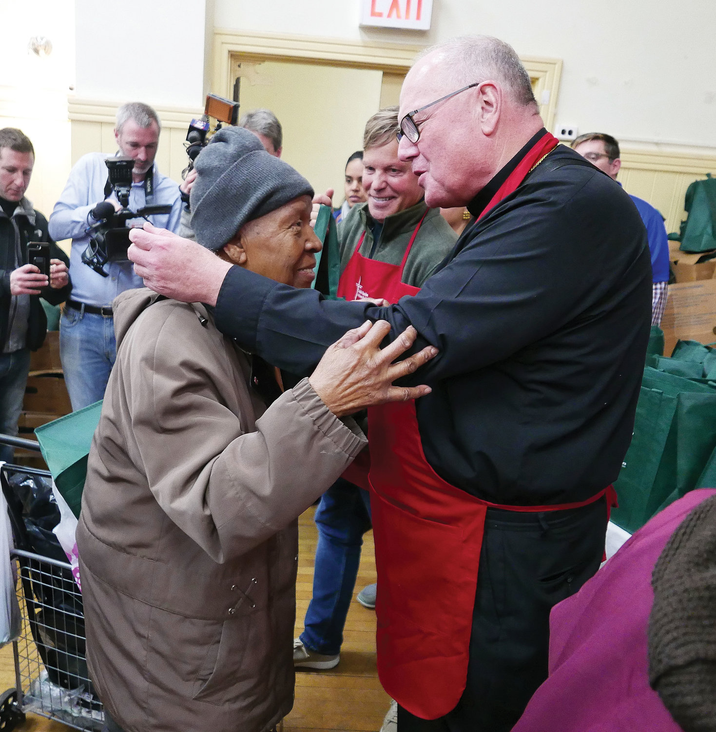 Cardinal Dolan meets with Cardinal Hayes High School students who were among the volunteers to set up the food display the night before the Catholic Charities' annual turkey distribution and lunch at the Lt. Joseph P. Kennedy Community Center in Harlem Nov. 20.
