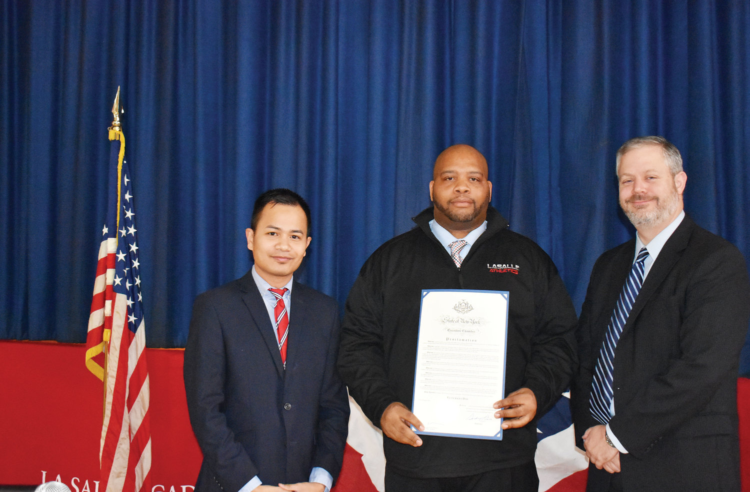 Jerome Pannell, center, La Salle's assistant principal for students services and athletic director, accepts a proclamation by Gov. Andrew Cuomo to La Salle honoring Veterans Day.