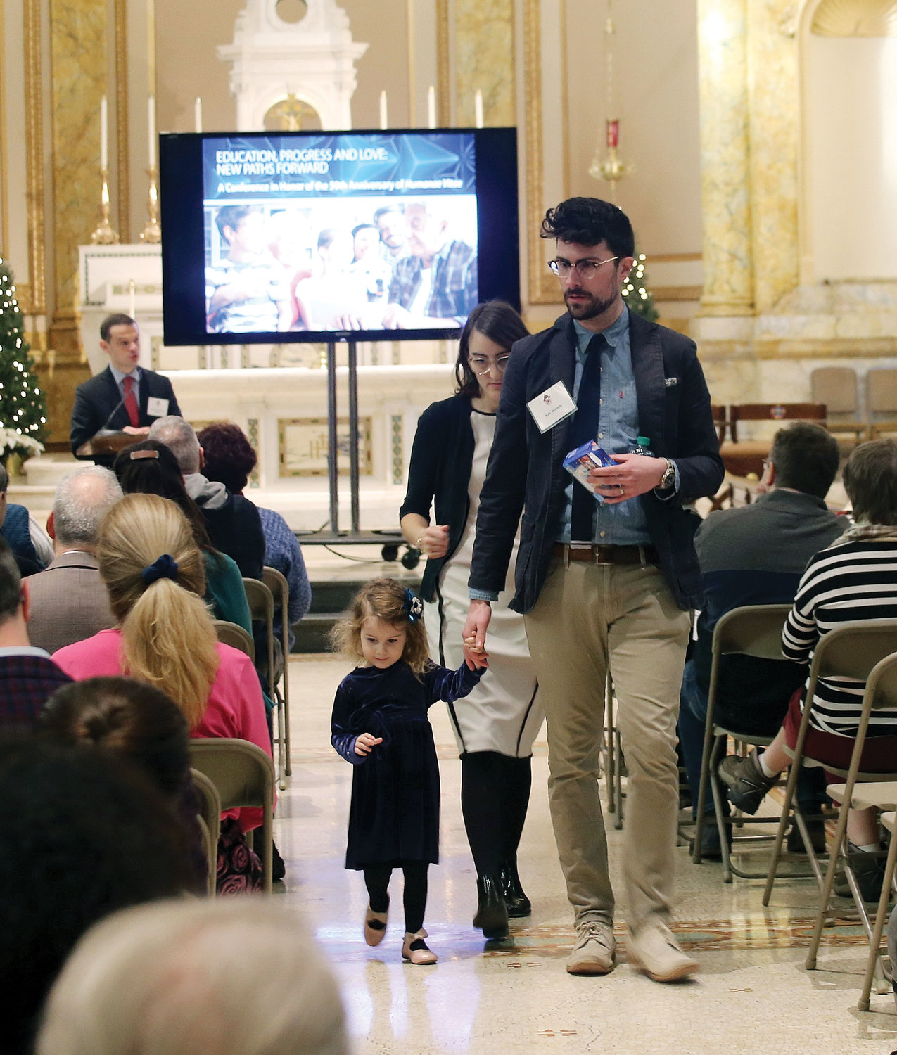 "Witness couple Cassie and Kyle Moriarty leave the podium with their 4-year-old daughter Amata at a conference about the gift of family, titled ""Education, Progress and Love: New Paths Forward,"" at St. Joseph's Seminary in Dunwoodie Dec. 1. The daylong gathering looked at the Catholic vision of family life in an ever-changing world."