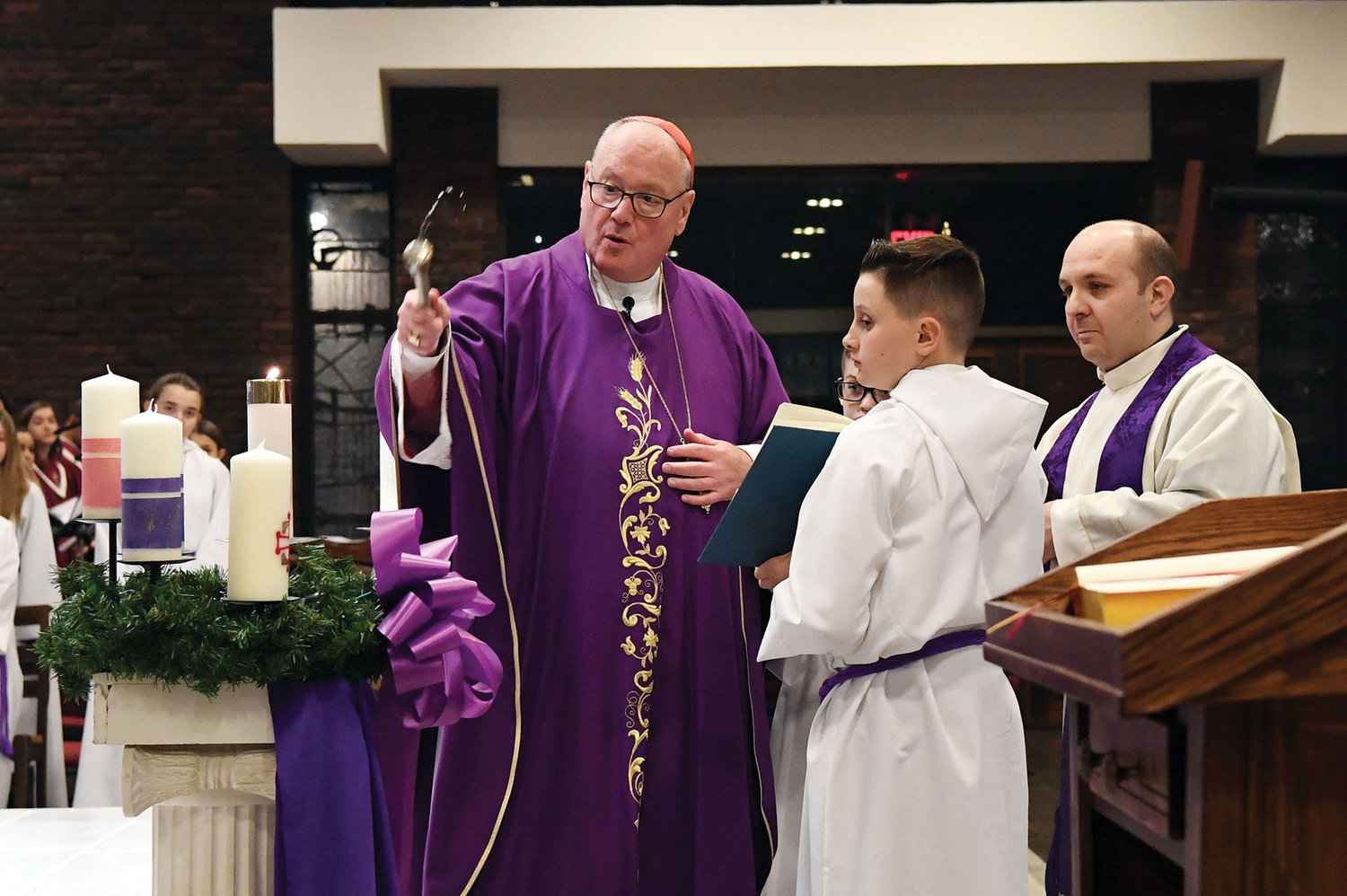 Cardinal Dolan sprinkles the Advent wreath with holy water during the Vigil Mass for the first Sunday of Advent he celebrated at Our Lady of Good Counsel Church on Staten Island Dec. 1. The bilingual liturgy was offered in English and Spanish, and a parish reception followed. Father Ambrose Madu is the pastor of Our Lady of Good Counsel.