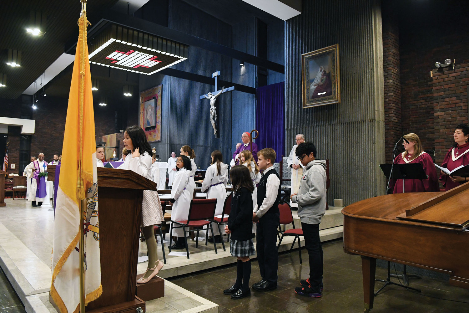 Students of the parish school and religious education program read the prayers of the faithful; at the microphone is Ariela Fuentes, 9.