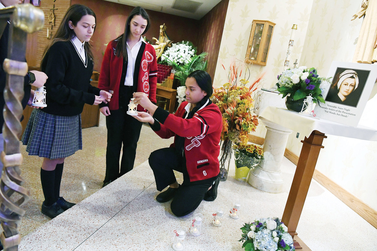 "Elizabeth Brown, a senior at Moore Catholic High School on Staten Island, alongside her peers, places lanterns at the base of a shrine to Venerable Honora ""Nano"" Nagle, foundress of the Sisters of the Presentation of the Blessed Virgin Mary. Moore Catholic hosted a Mass Nov. 18 at Our Lady of Pity Church on Staten Island in honor of Venerable Nagle's 300th birthday."