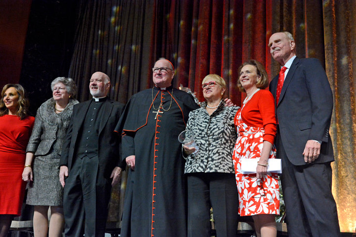 "GOOD COMPANY—At the Cardinal's Christmas Luncheon at the New York Hilton Midtown were Rosanna Scotto, co-host of ""Good Day New York""; Mary Buckley Teatum, president of the Ladies of Charity; Msgr. Kevin Sullivan, executive director of archdiocesan Catholic Charities; Cardinal Dolan; and honorees Lidia Bastianich and Catherine and Christopher Kinney."