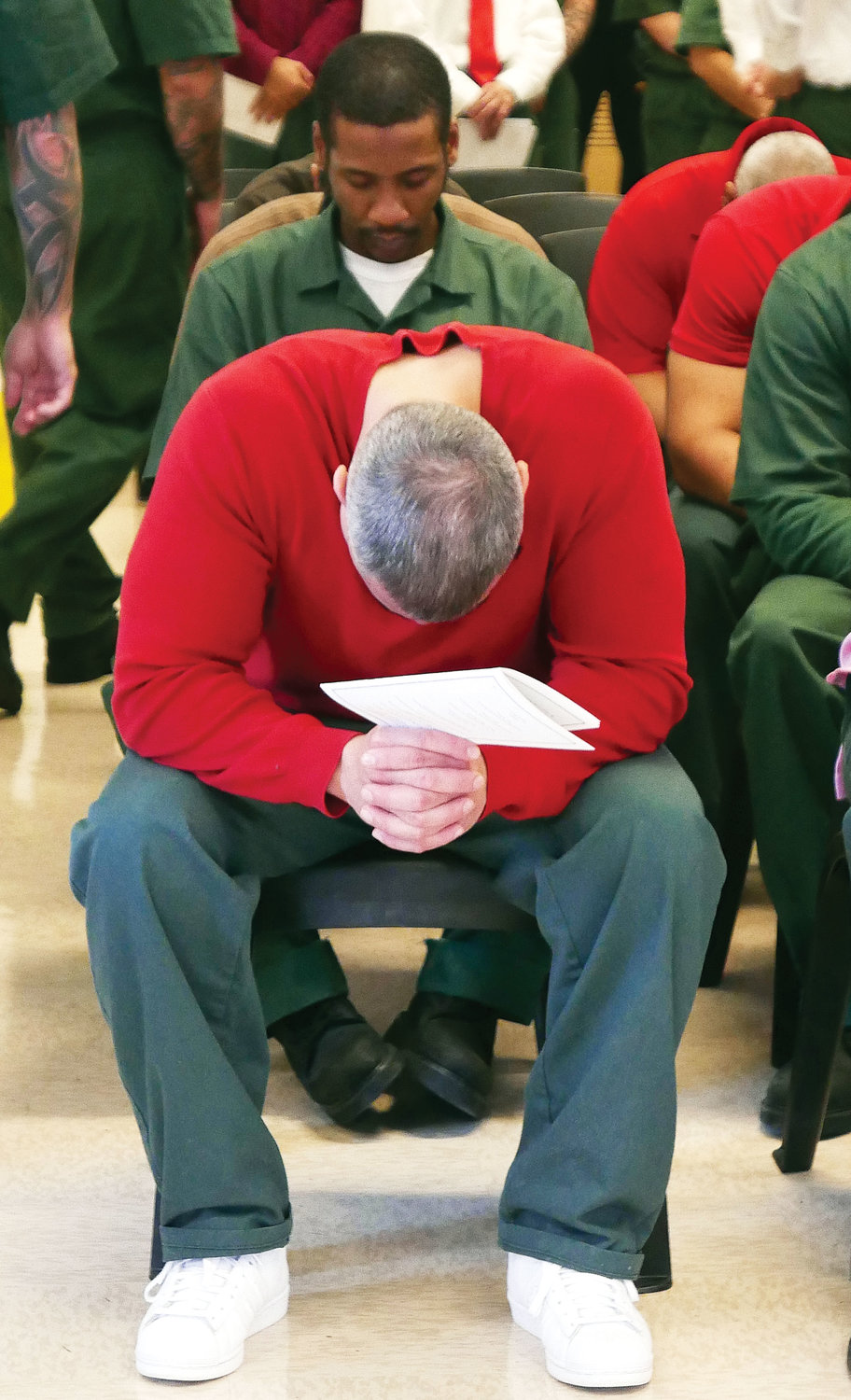 Inmates bow their heads in prayer during Mass.