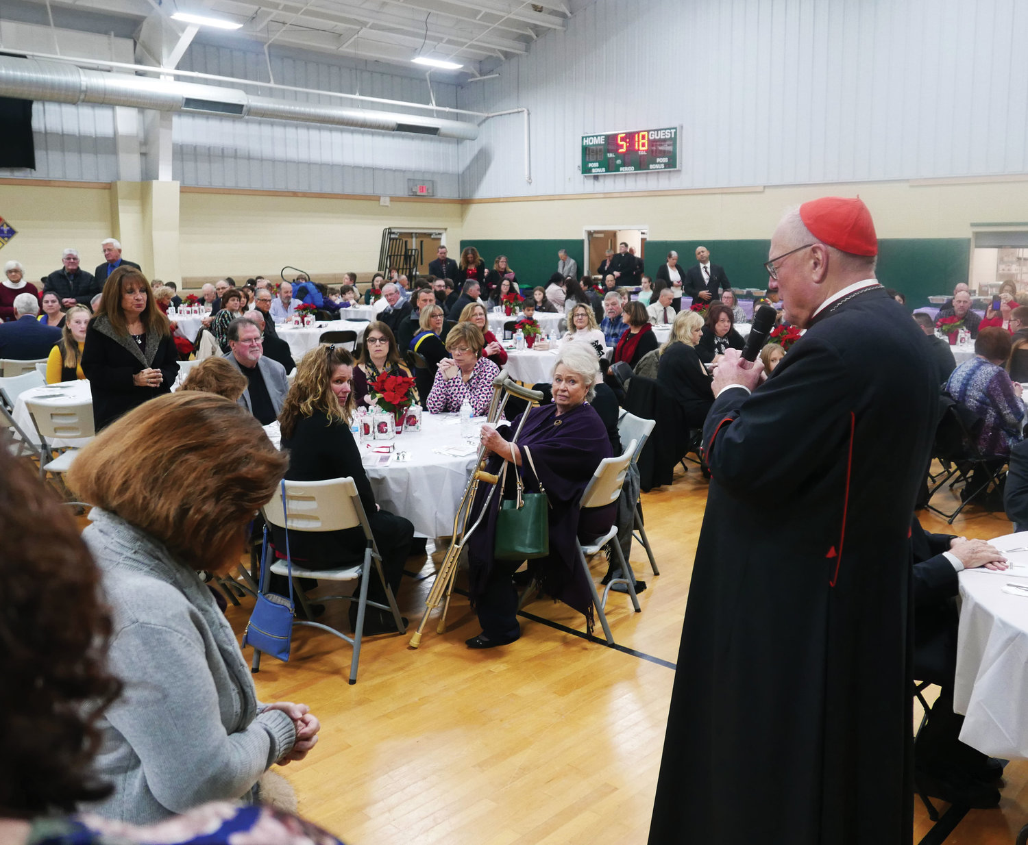 Cardinal Dolan leads prayer before a buffet meal is served at a reception in the parish center following Mass.