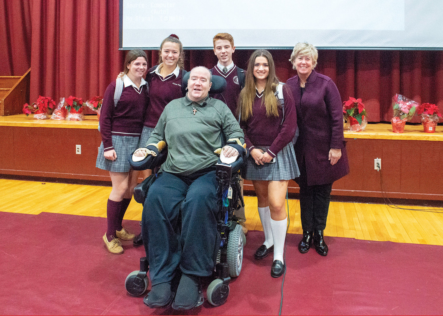 Billy Keenan and Patti Ann McDonald, widow of the late NYPD Det. Steven McDonald, greet students Flynn Kirk, Morgan Adams, Kieran Keenan, who is Billy's son, and Alexa Gabrielle in Tom Collins Gymnasium at Albertus Magnus High School in Bardonia Dec. 11.